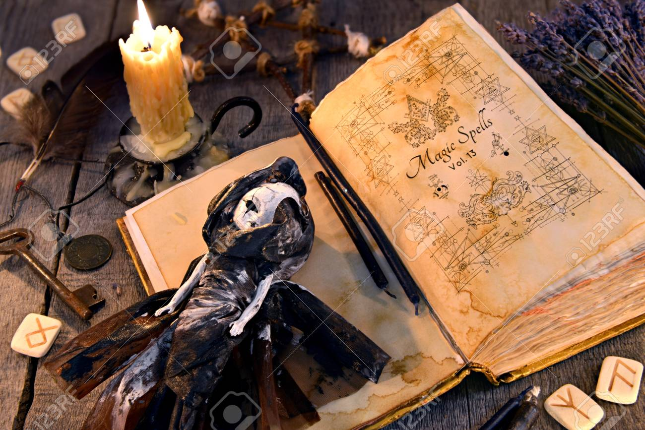 Old book with black magic spells, scary doll, rune and burning