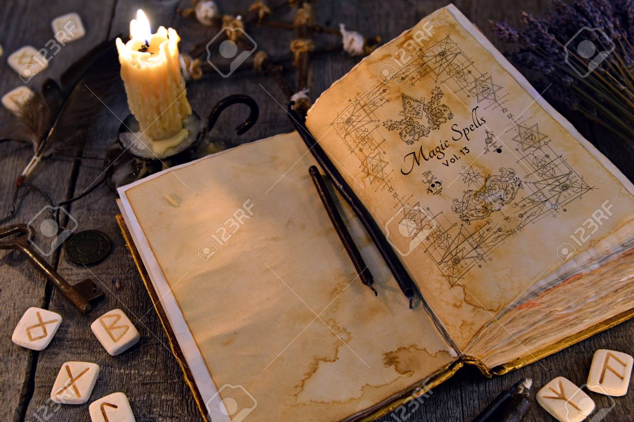 Open old book with magic spells, runes, candle and key on witch
