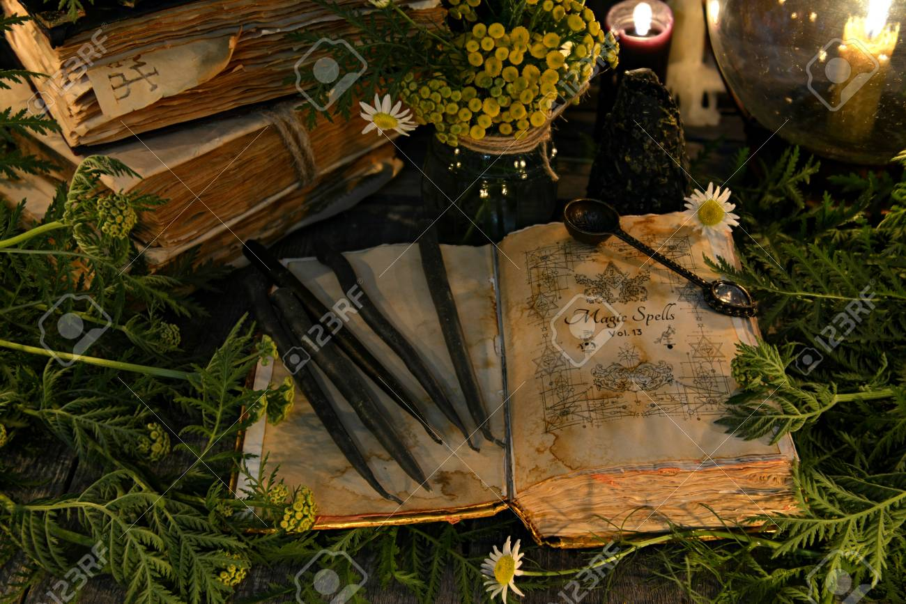 Open book with magic spells, black candles and with herbs in