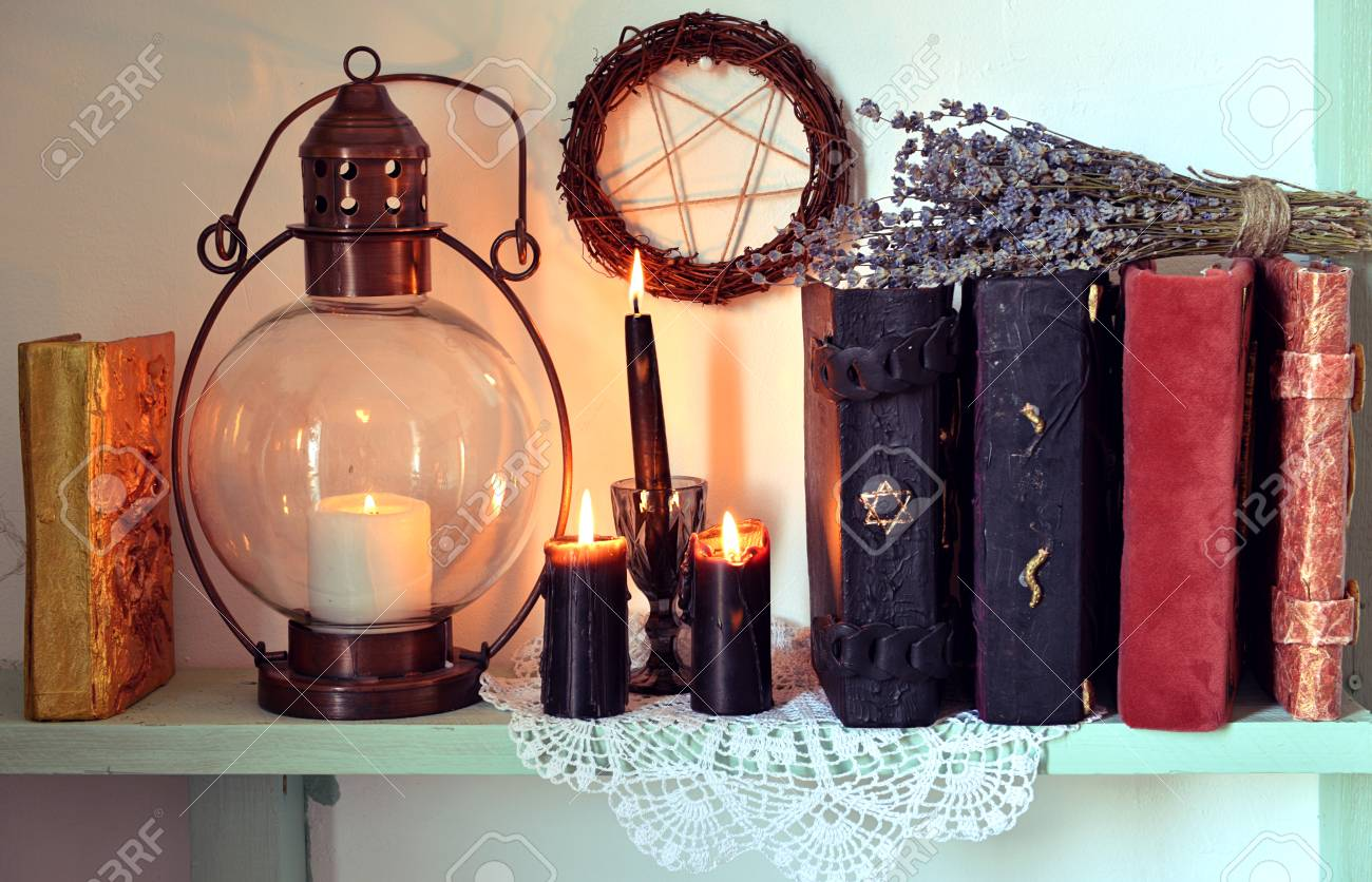Witch shelf with magic books, old lamp, black candles and lavender