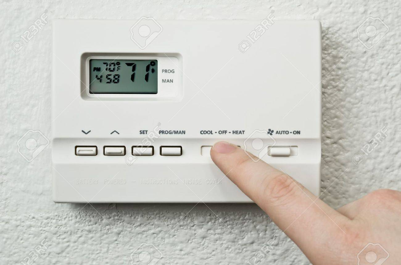 digital thermostat and finger pressing button Stock Photo - 12421915