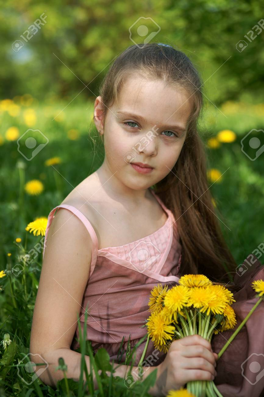 Little girl sits on glade with dandelions Stock Photo - 13413205