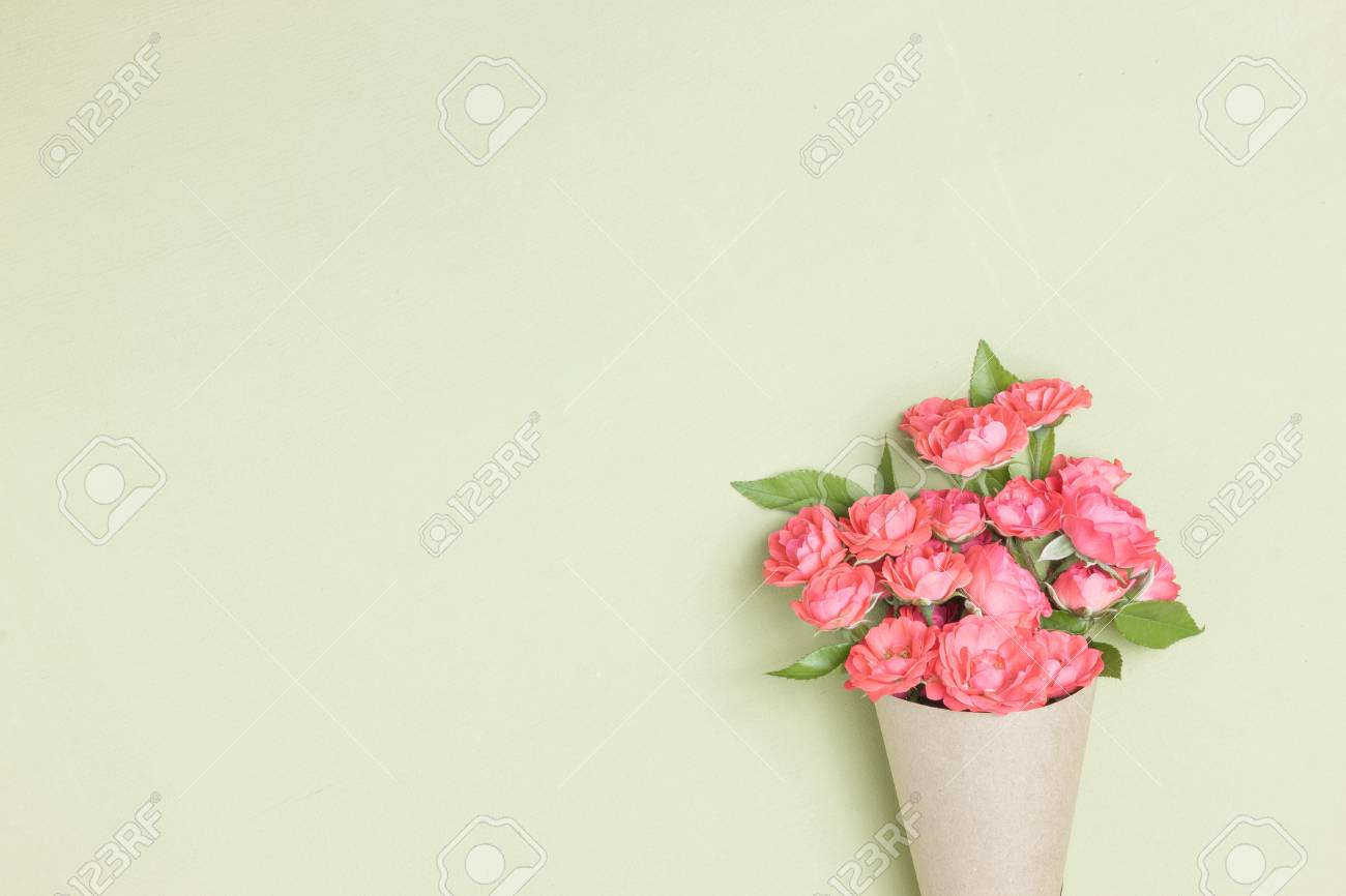 Bouquet Of Small Red Roses In Vintage Paper On The Table Top