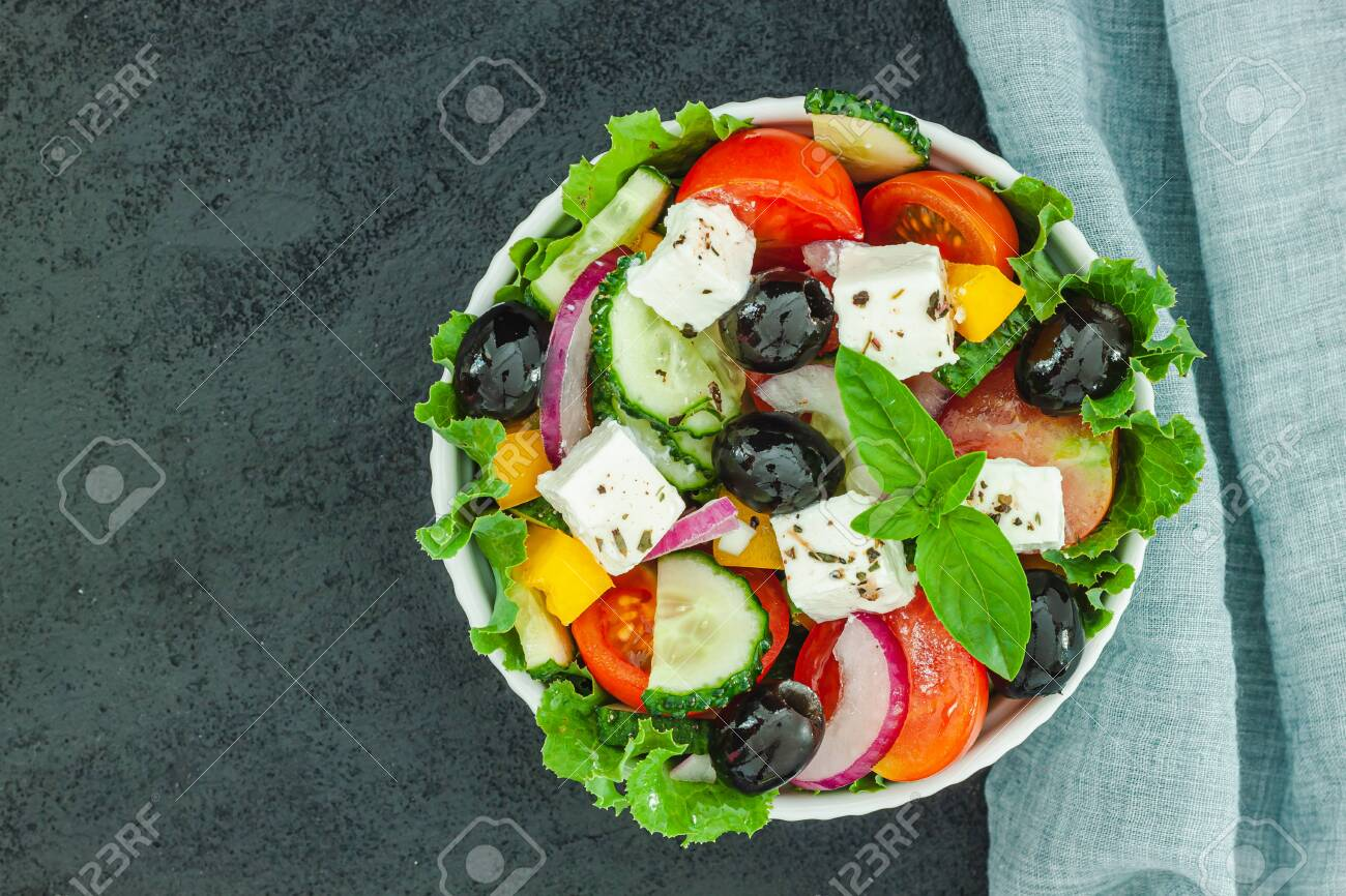 Greek salad with tomato and fresh vegetables in white bowl on dark balck background. Top view - 153505419