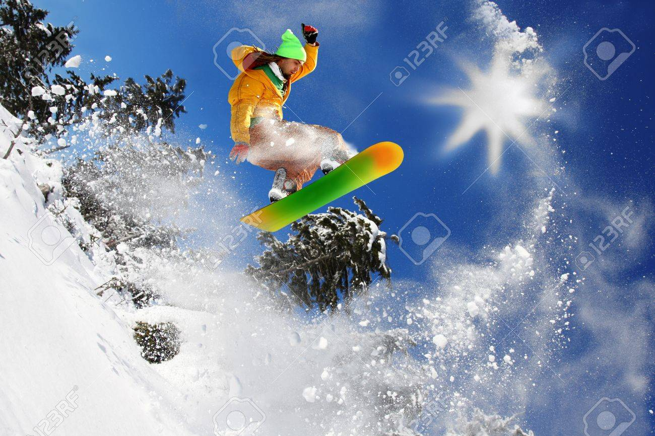 Snowboarders jumping against blue sky Stock Photo - 12021303