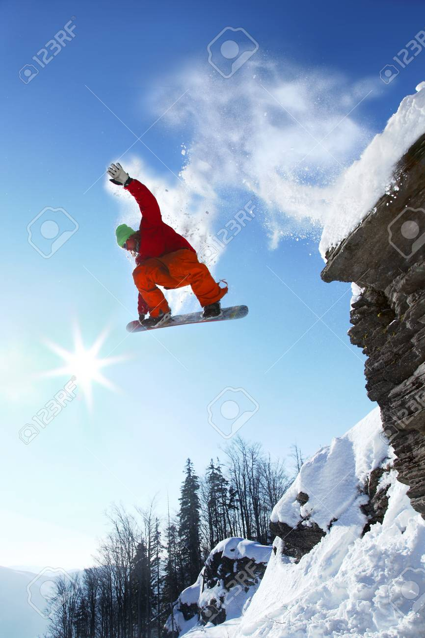 Snowboarder jumping against blue sky - 15981088