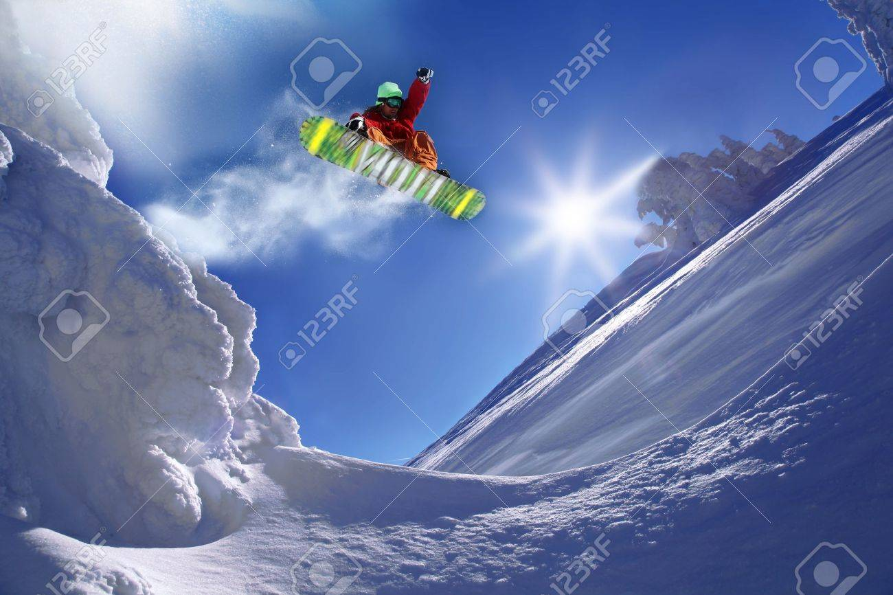 Snowboarder jumping against blue sky - 15981090