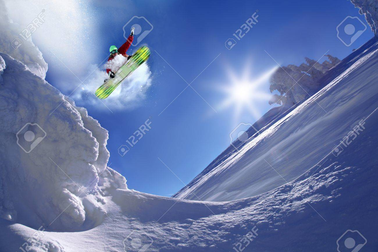 Snowboarder jumping against blue sky - 15981089