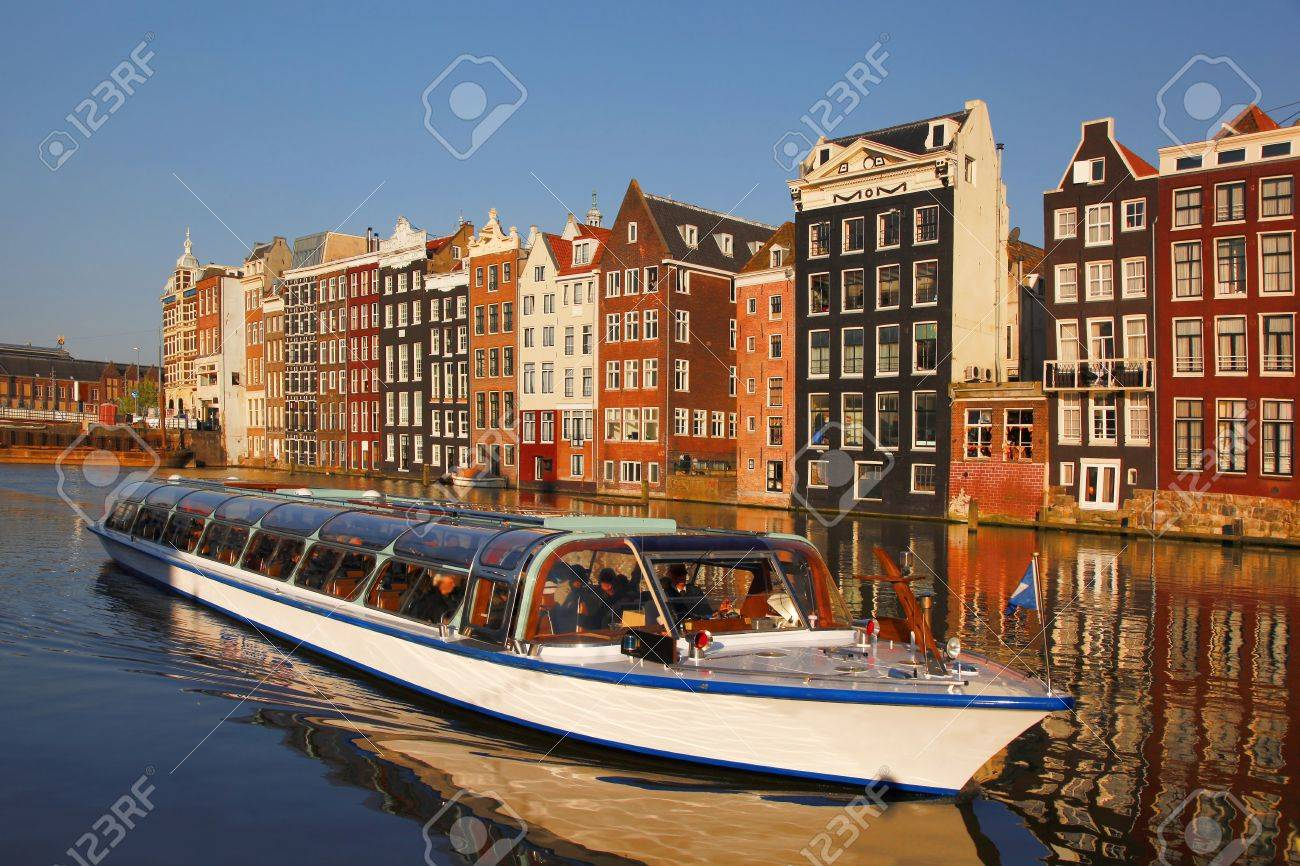 Amsterdam with tourist boat on canal in Netherlands - 19548764