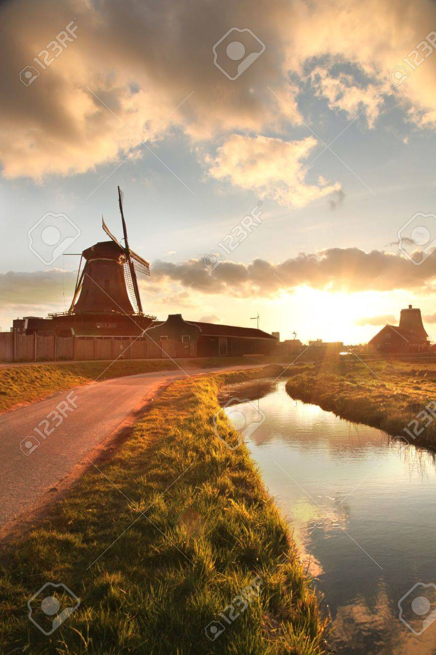 Traditional Dutch windmills with canal against sunset in Amsterdam area, Holland - 19891482