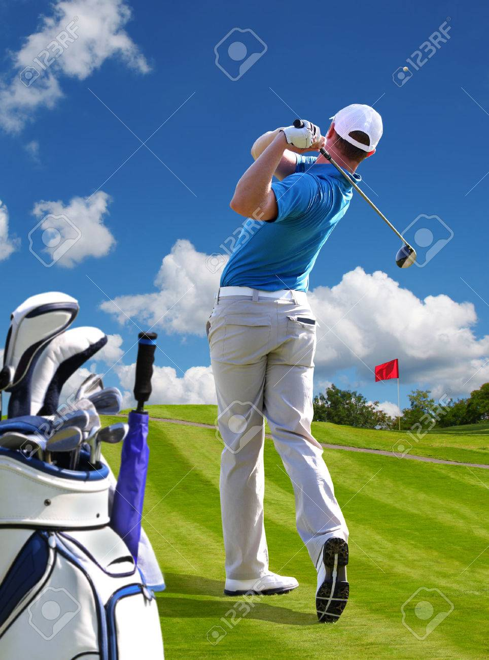 Man playing golf against blue sky with golf bag Stock Photo - 26016252