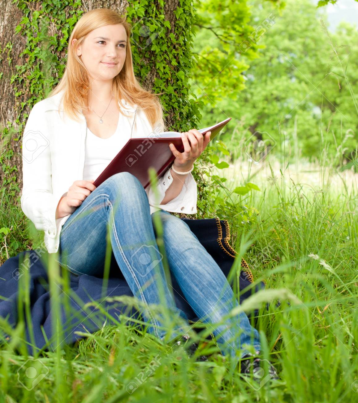 Beautiful young woman reading a book outdoors on a grass field in park Stock Photo - 9515995