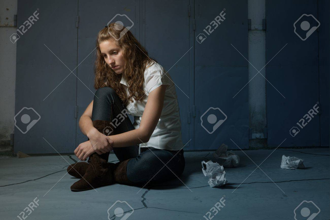 Sad lone girl sitting on flor in darkness Stock Photo - 11682352