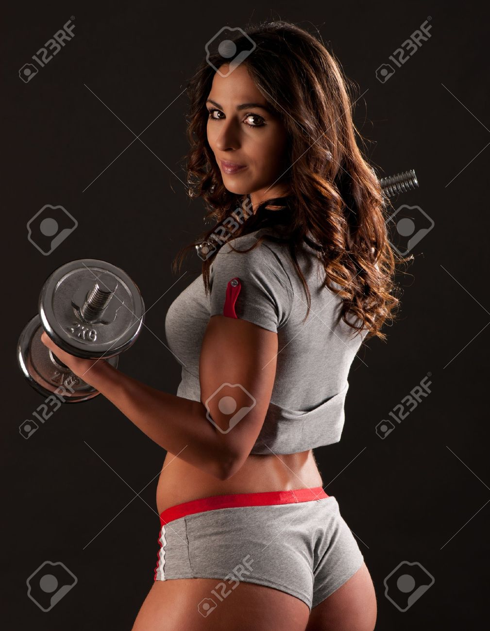Young fit girl working out with weights - Portrait of pretty young woman lifting dumbbells during exercising Stock Photo - 12728506