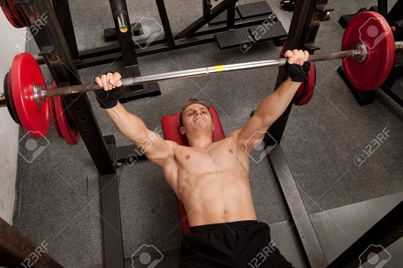 Man exercising his arm muscles by lifting two dumbell free weights in a fitness club Stock Photo - 13233087