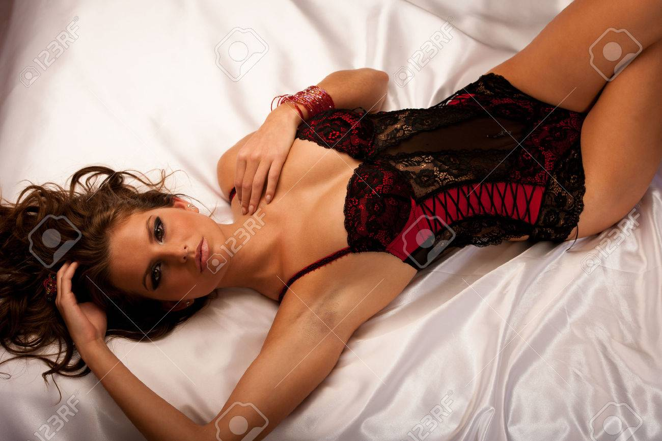 Beautiful young woman wearing black and red lingerie in bed Stock Photo - 24099485