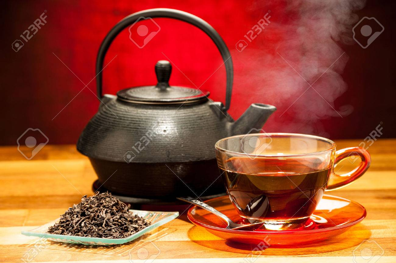 a cup of black tea with teapot in the background Stock Photo - 23858907