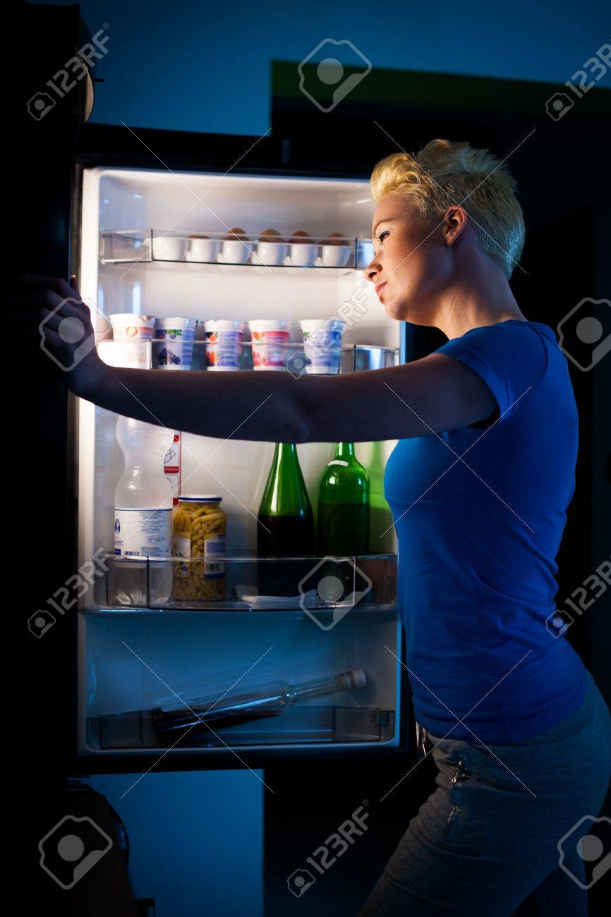 Hungry woman searching for food in refregirator late at night Stock Photo - 29125904