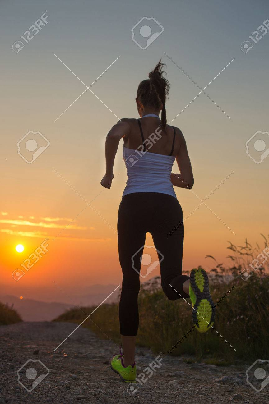 woman running outdoor on a mountain road at summer sunset Stock Photo - 32308534