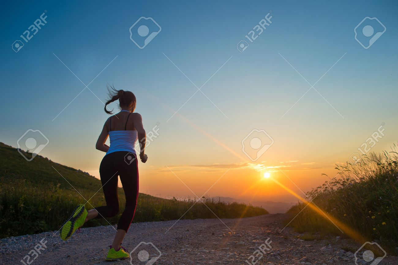 woman running outdoor on a mountain road at summer sunset Stock Photo - 32308535