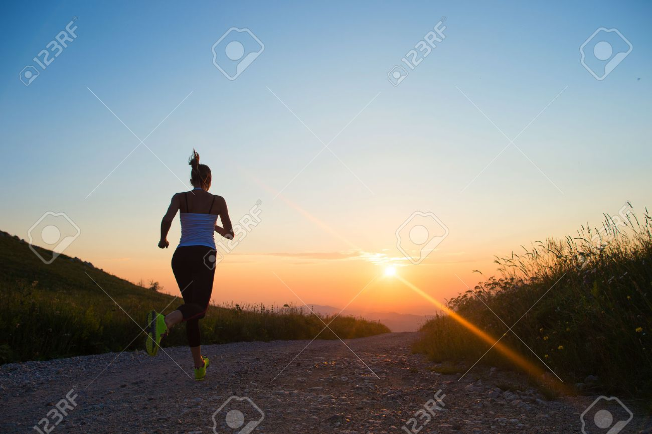 woman running outdoor on a mountain road at summer sunset Stock Photo - 32646263