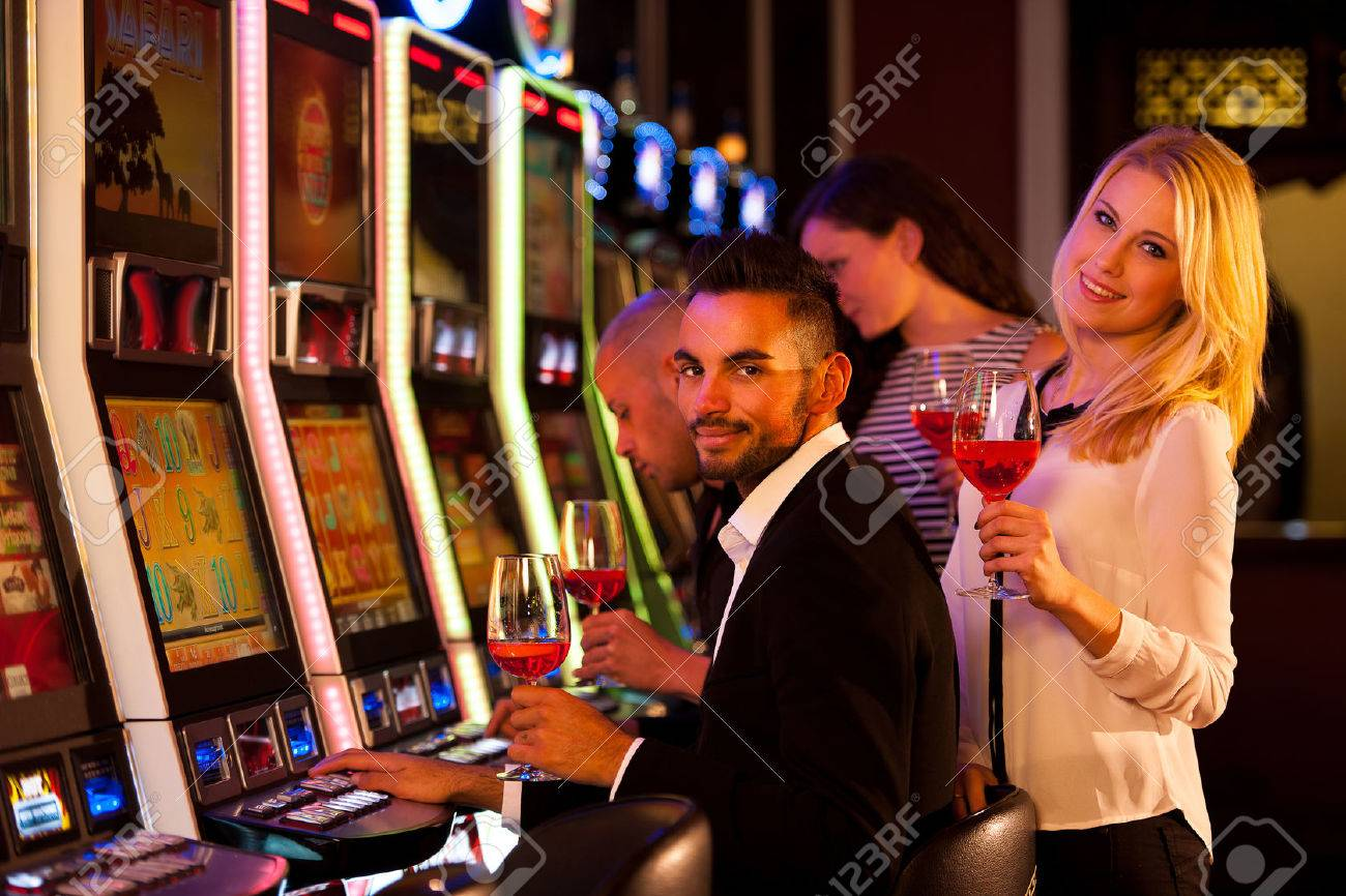 young people playing slot machines in casino Stock Photo - 35656504