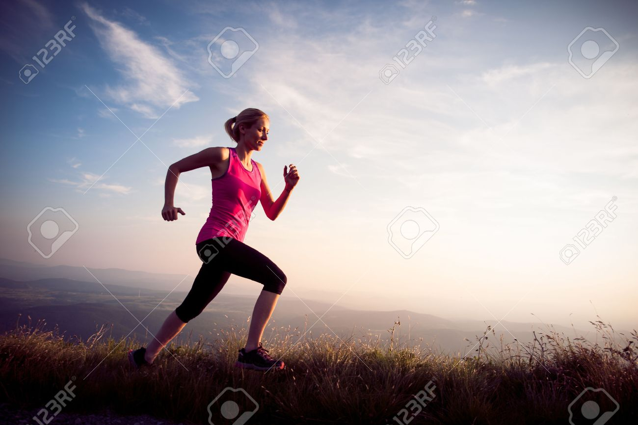 beautiful young woman runns on a mountian path at sunrise Stock Photo - 45452410