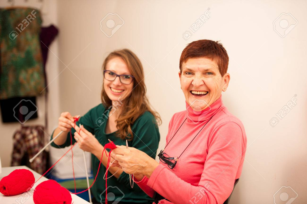 Women knitting with red wool. Eldery woman transfering her knowledge of knitting on a younger woman on handcraft workshop. Stock Photo - 51503951