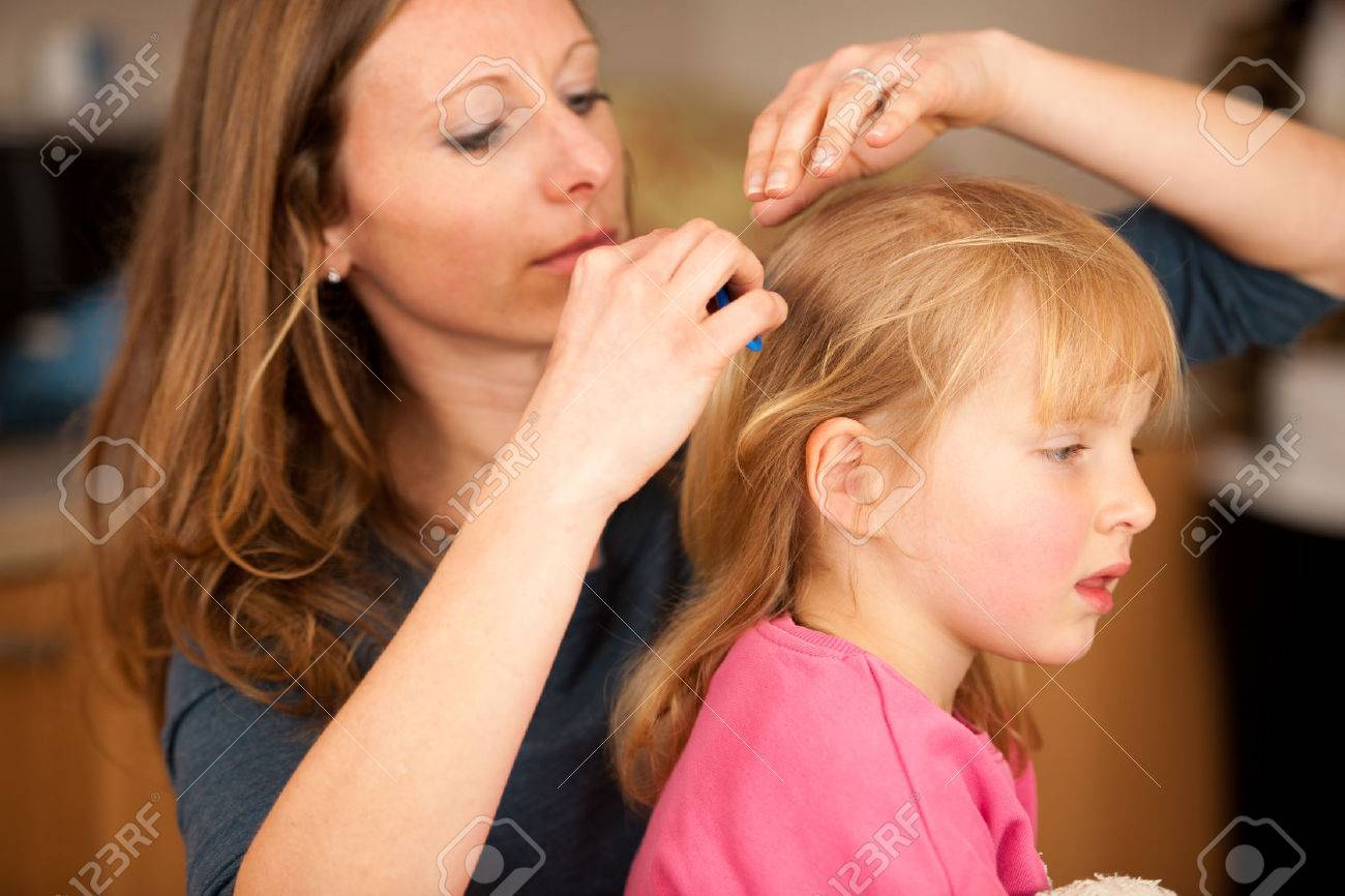 Mother combs hair to a cute little girl Stock Photo - 63148031