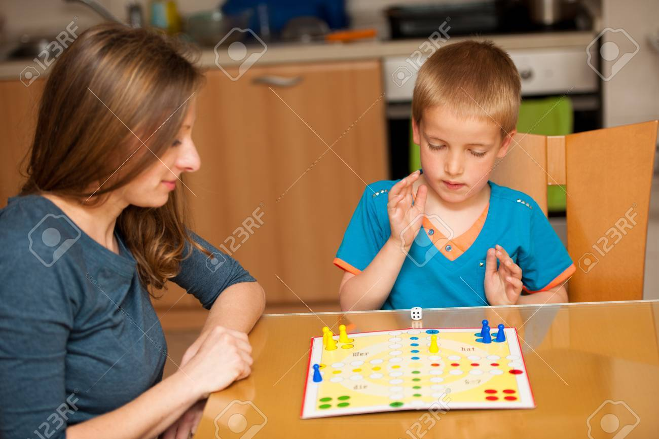 Young Boy Plays Ludo Game With His Mother On A Table In Livingroom