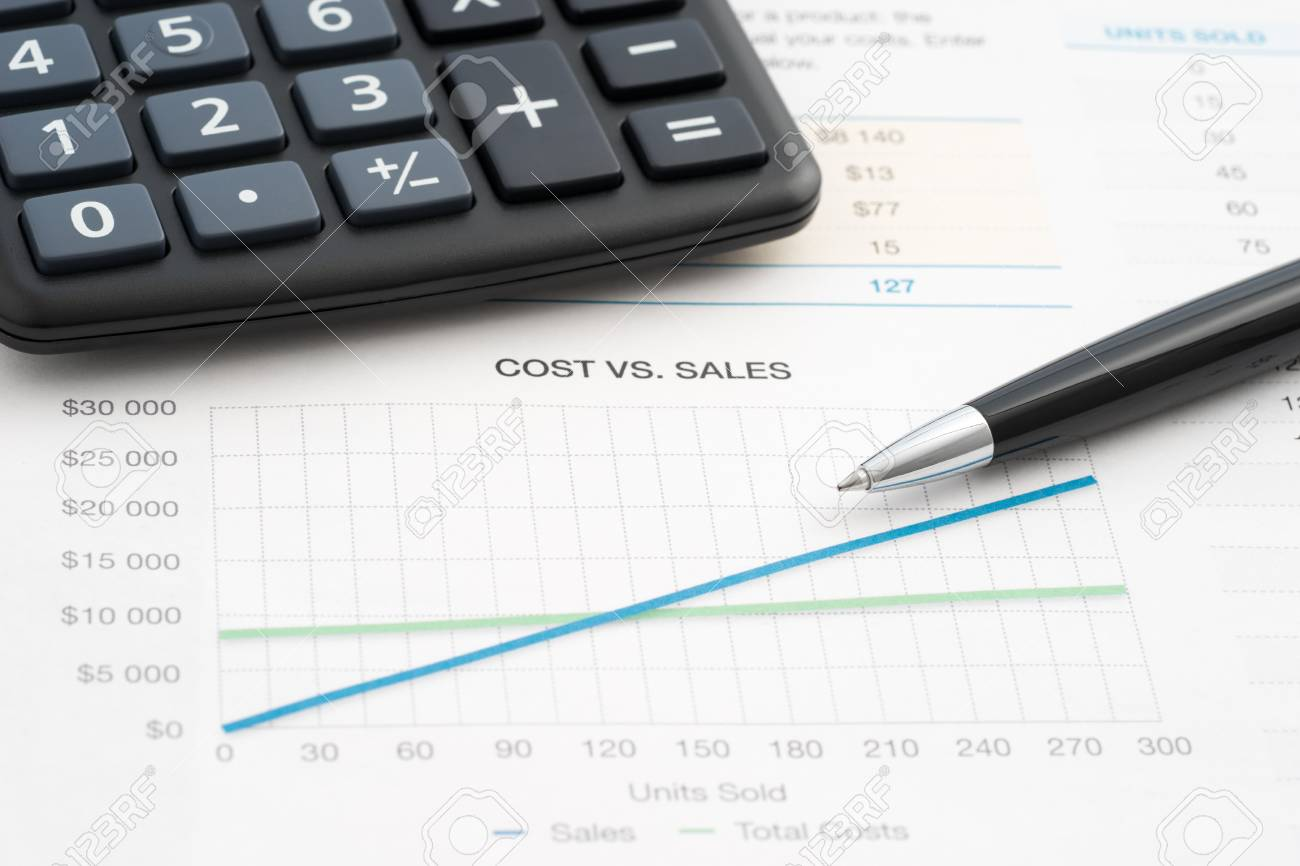business reports cost vs sales calculator and pen stock photo