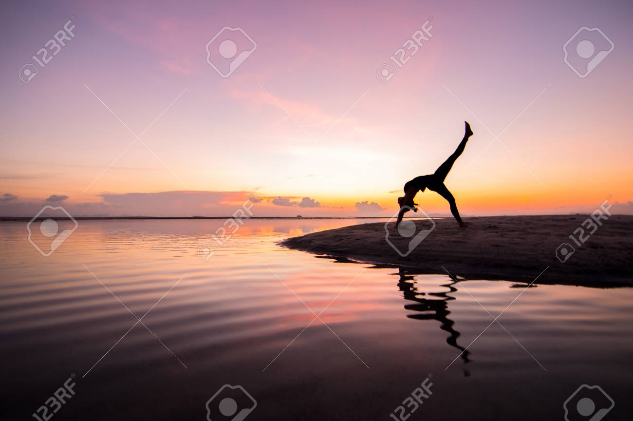 Silhouette woman with yoga posure on the beach at sunset with reflection. Stock Photo - 23518744