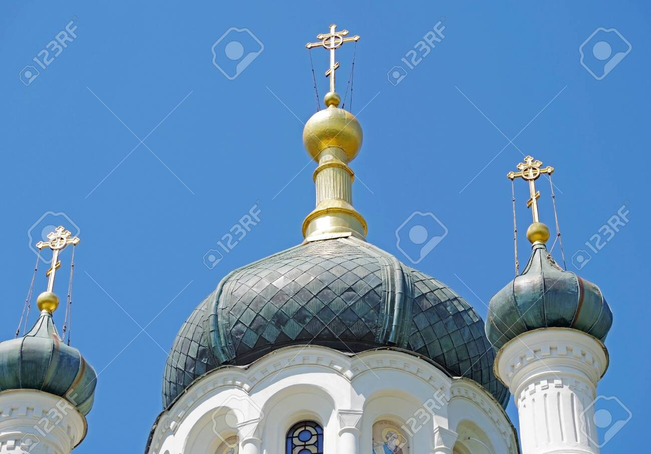 The dome of the Church with a cross against the blue sky - 124509105