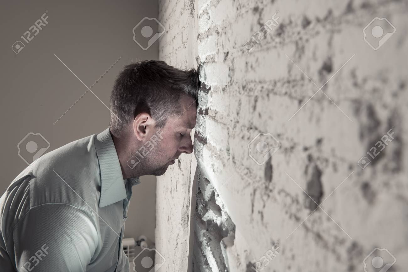 Depressed Man Leaning Up On A White Wall In Dark Room At Home Stock Photo Picture And Royalty Free Image Image 109694824