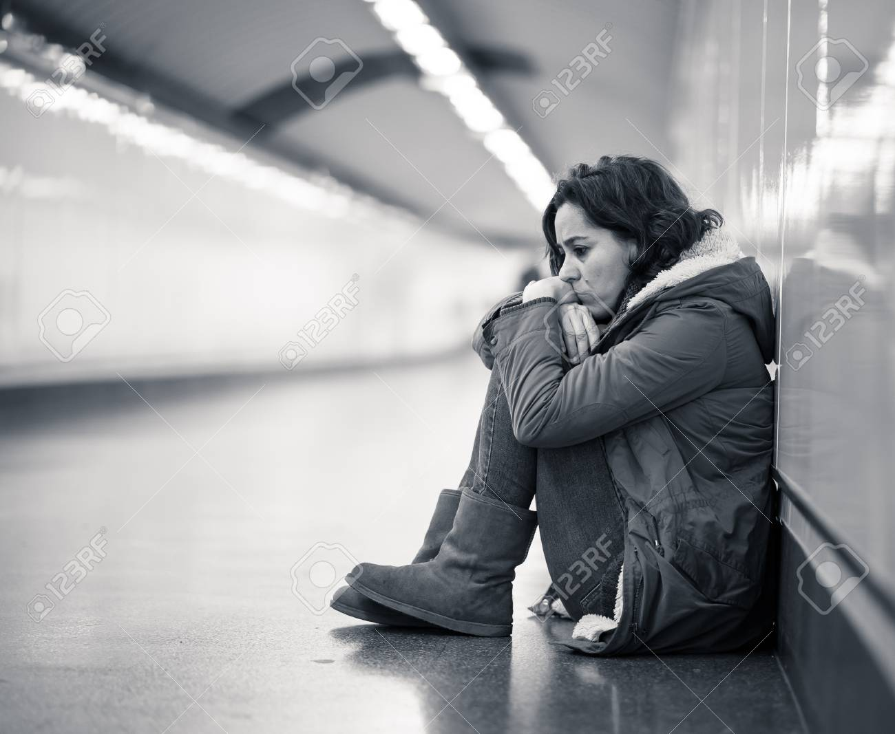 Stock photo young adult felling shame depressed and hopeless sitting alone on subway city ground in depression loneliness mental health emotional pain