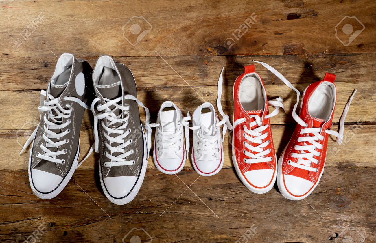 Conceptual image of gumshoes sneakers shoes of father mother and son daughter family on vintage wood floor in different sizes in Sweet home togetherness Happy Family Parenting and lifestyle concept. - 123597205