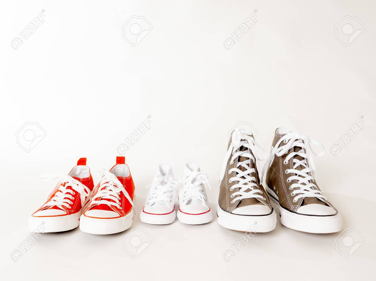 Conceptual image of gumshoes sneakers of father mother and son daughter isolated on white background copy space in different sizes in togetherness Family Parenting Education and lifestyle concept. - 123598780