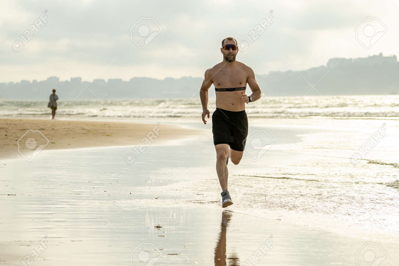 Sports fitness man with heart rate monitor running on beach with smart watch. Fit body male runner doing jogging workout at the sea in sport exercise and technology and healthy lifestyle concept. - 151571736