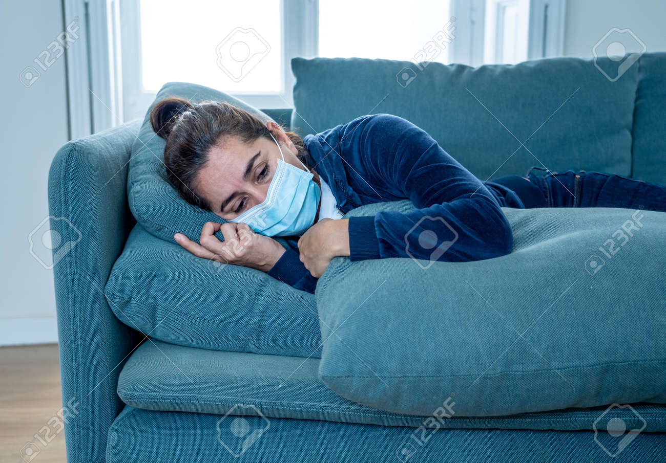Sad latin woman with protective face mask at home living room couch feeling tired and worried suffering depression amid lockdown and social distancing. Mental Health and isolation concept. - 165490528