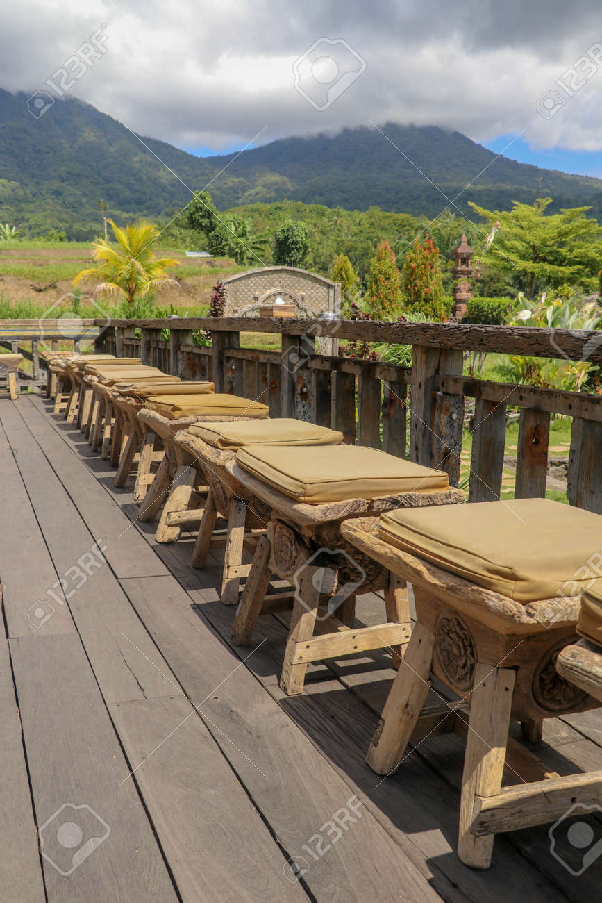Row of wooden stools with cushions on terrace with floor made of planed wooden planks. It bumps from roughly worked beams. Background with mountains whose peaks are shrouded in thick clouds. Sunny day. - 147064663