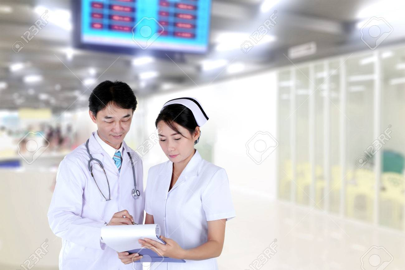 Medecin Et Une Infirmiere Examinant Le Dossier Medical A L Hopital