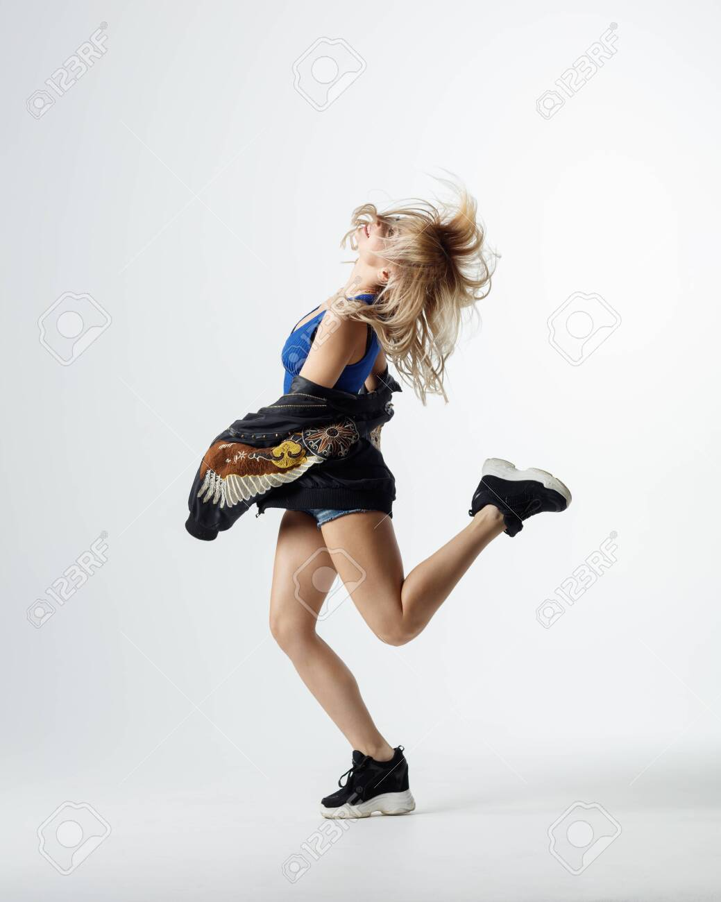 Hip hop dancer moving and jumping in photostudio - 120484860