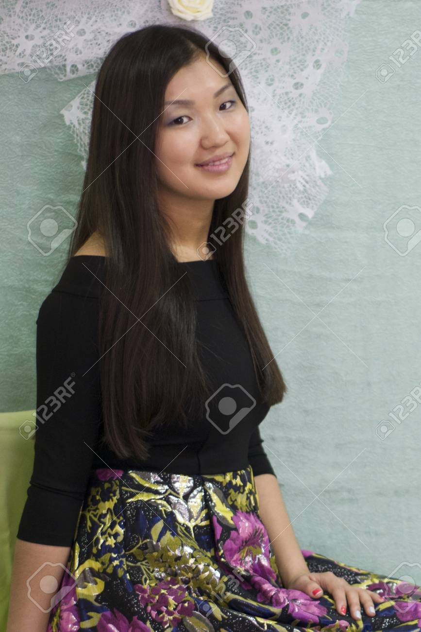 beautiful japanese girl sitting on a chair in the studio. stock