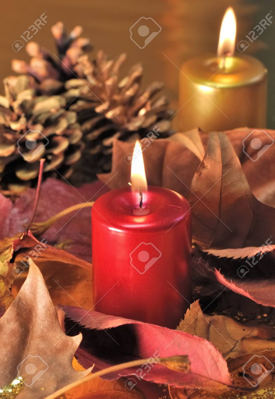 Red and golden candles lit  with leaves and pine cones on a golden background Stock Photo - 11557872