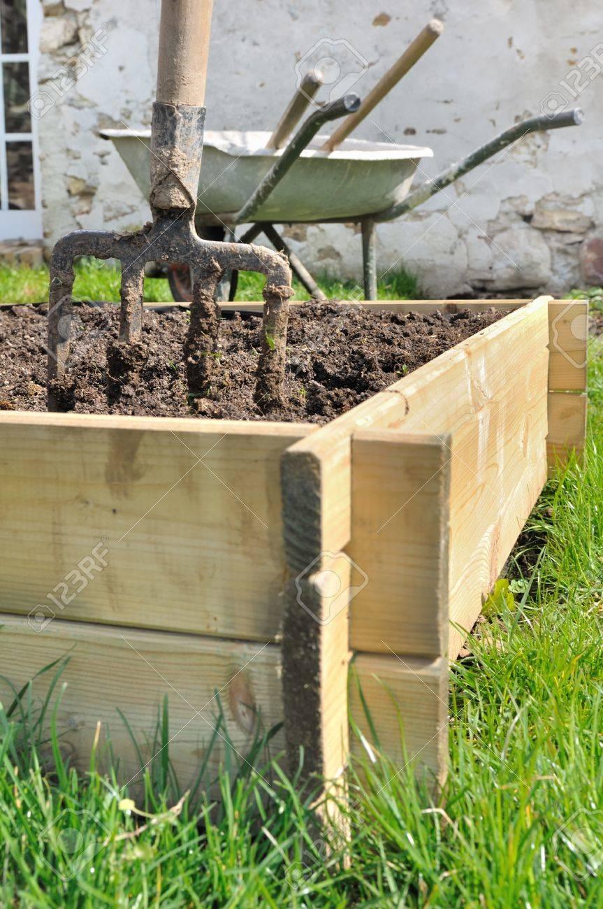 Potager Mobile En Bois bêche dans une jardinière en bois pour le jardin potager