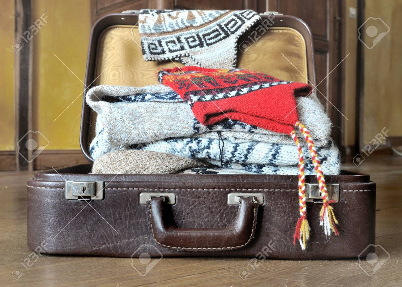 dc113653ecc open suitcase full of warm clothes on the floor Stock Photo - 51470859