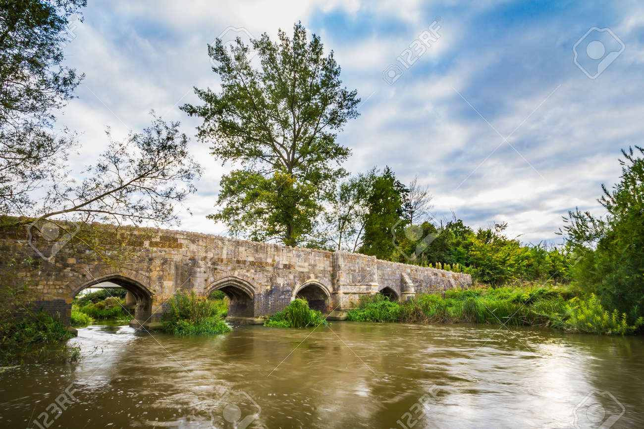 Old stone medival bridge over a streaming river in England. Dramatic cloudscape and old color tones - 123118055