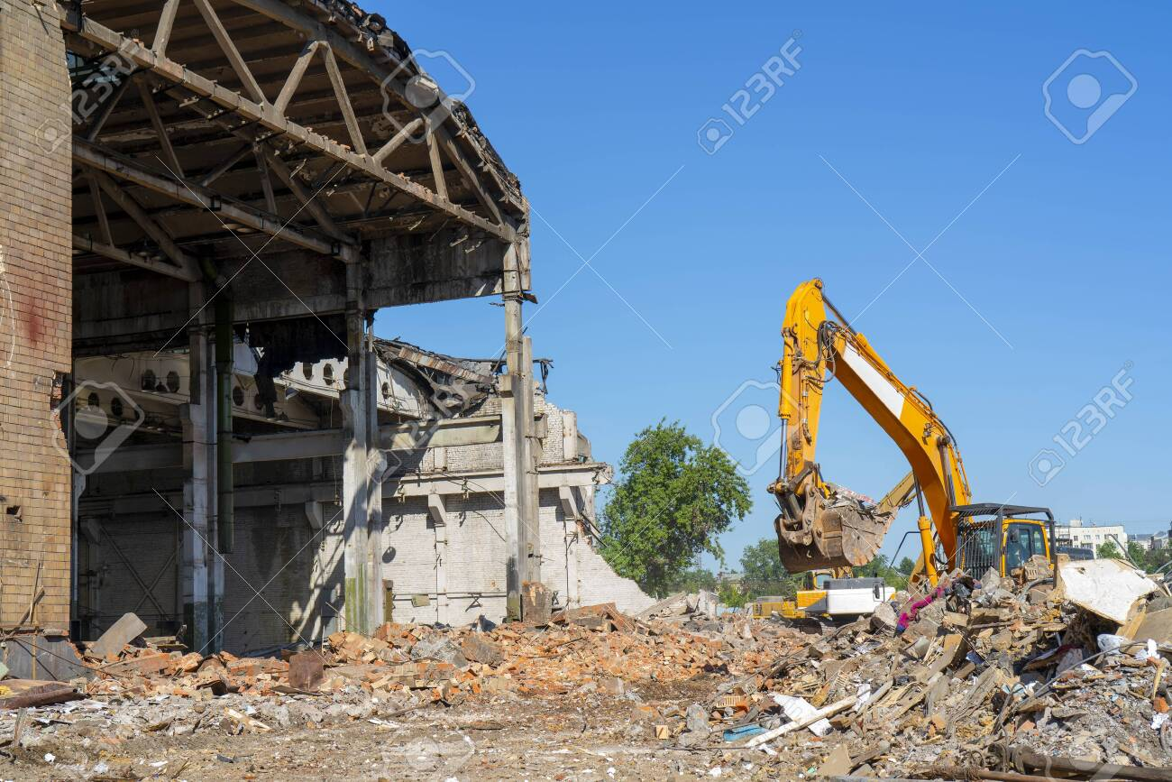Destruction of the old building. Yellow excavator on the ruins. - 123631176