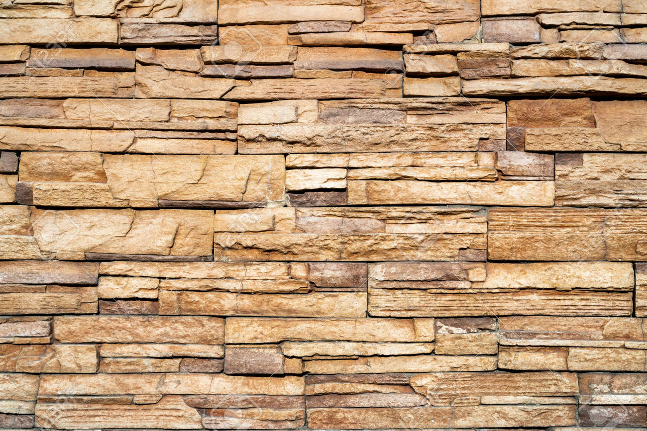 Wall of yellow stone. Abstract natural background. Uneven stone surface. - 168292037