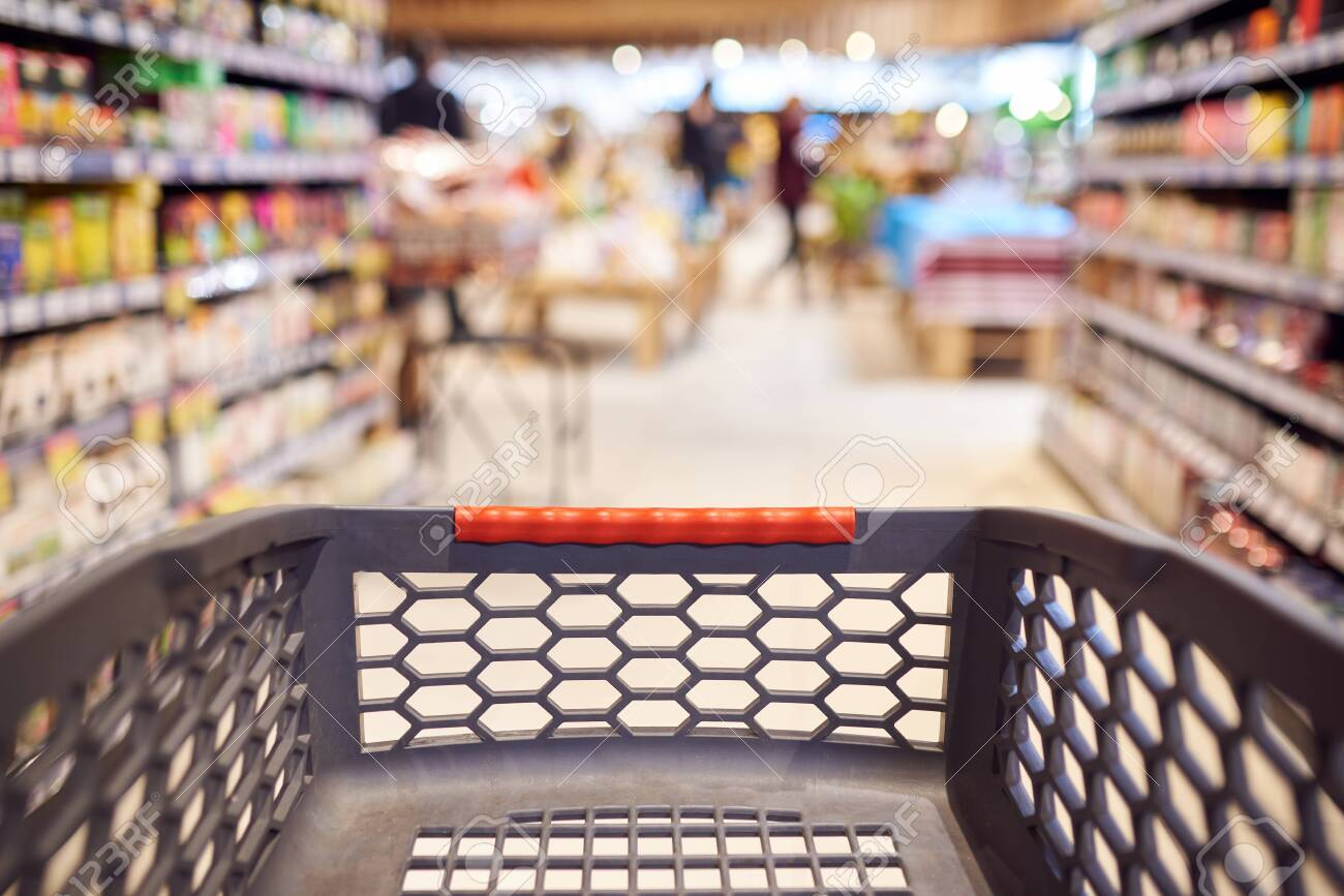 Abstract blurred photo of empty trolley in supermarket bokeh background. Empty shopping cart in supermarket. - 144401754